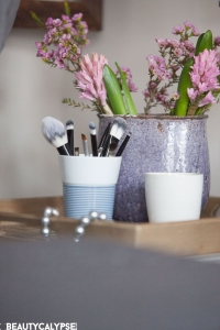 Nightsstand with scented candle, flowers, and brushes in a Kahla cupit cup